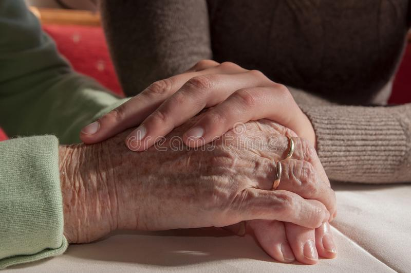 Jovem mulher que guarda as mãos da mulher superior triste com cadeira de rodas foto de stock