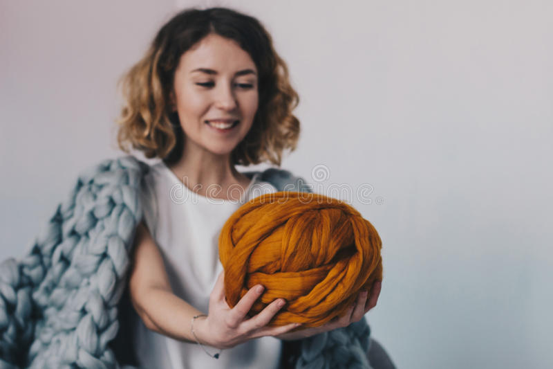 Jovem mulher que guarda a bola alaranjada de lãs do merino foto de stock royalty free
