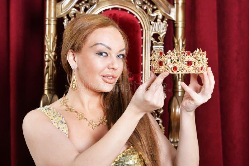 Jovem mulher que guarda a coroa rainha foto de stock
