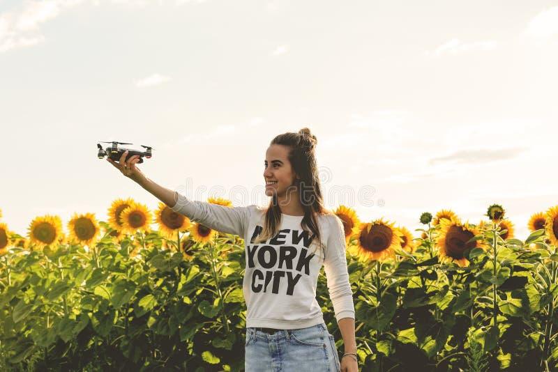 Jovem mulher que guarda disponível o mini zangão de voo fora fotos de stock