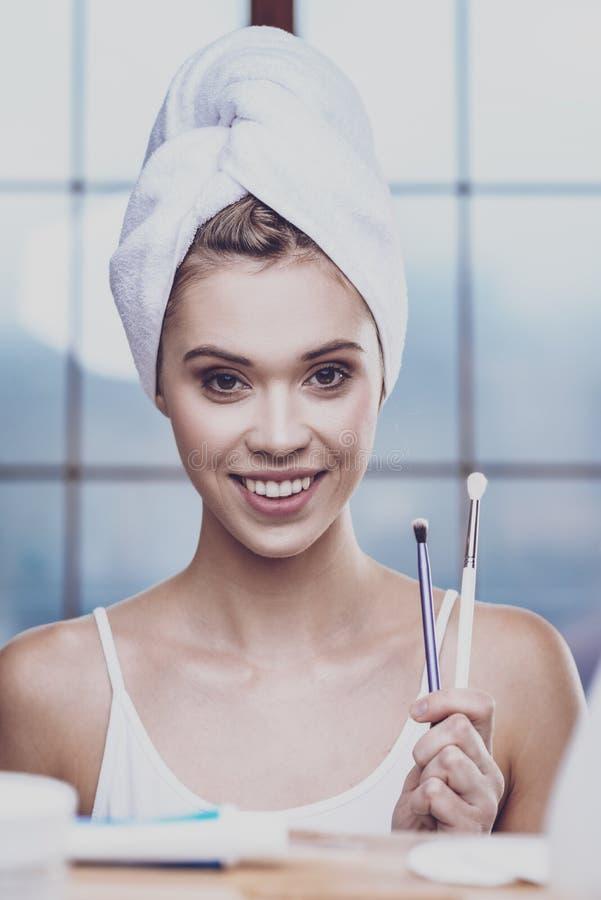 A jovem mulher que guarda escovas para compõe imagens de stock royalty free