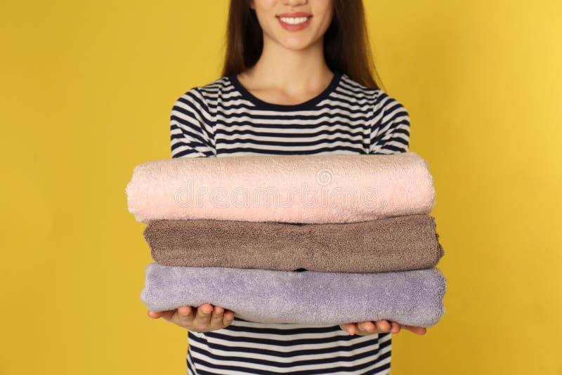Jovem mulher que guarda a lavanderia limpa no fundo da cor imagem de stock royalty free