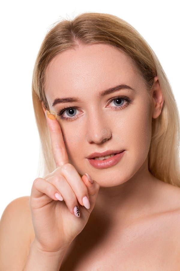 Jovem mulher que guarda a lente de contato no indicador com espaço da cópia Cara ascendente próxima da mulher bonita saudável apr fotografia de stock royalty free