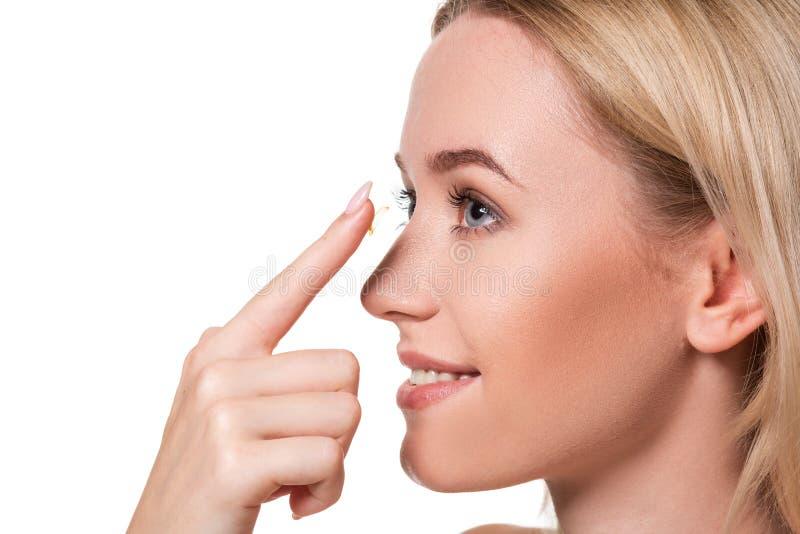 Jovem mulher que guarda a lente de contato no indicador com espaço da cópia Cara ascendente próxima da mulher bonita saudável apr imagem de stock