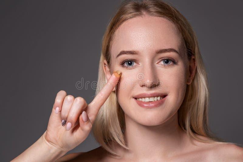 Jovem mulher que guarda a lente de contato no indicador com espaço da cópia Cara ascendente próxima da mulher bonita saudável apr fotos de stock royalty free