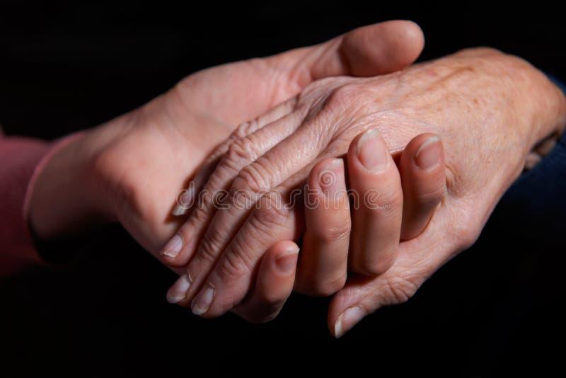Jovem mulher que guarda a mão de mulher mais idosa imagem de stock royalty free