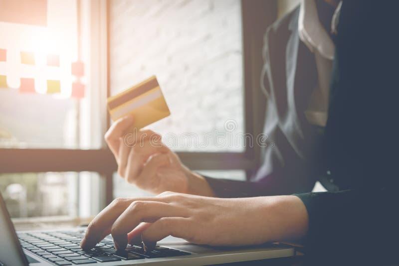 Jovem mulher que guarda o cartão de crédito e que usa o laptop Onlin fotos de stock