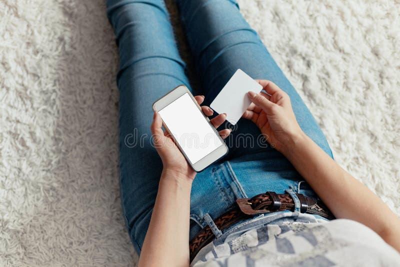 Jovem mulher que guarda o cart?o de cr?dito e que usa o assento do telefone no assoalho pagamento Conceito em linha da compra C foto de stock royalty free