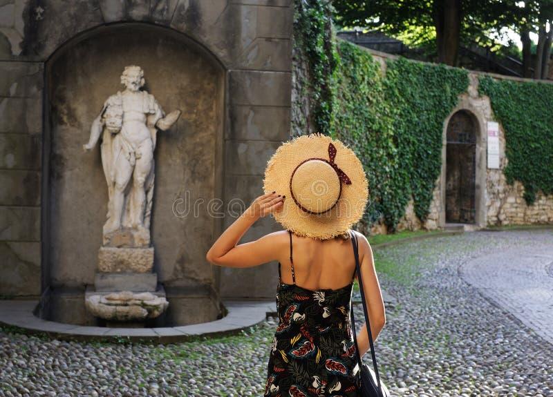 Jovem mulher que guarda o chapéu perto da estátua foto de stock