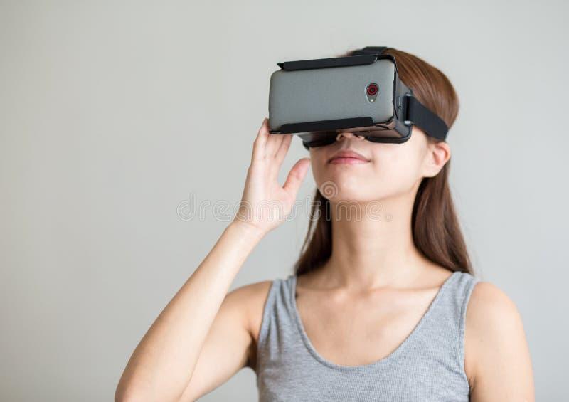 Jovem mulher que guarda o dispositivo da realidade virtual imagens de stock
