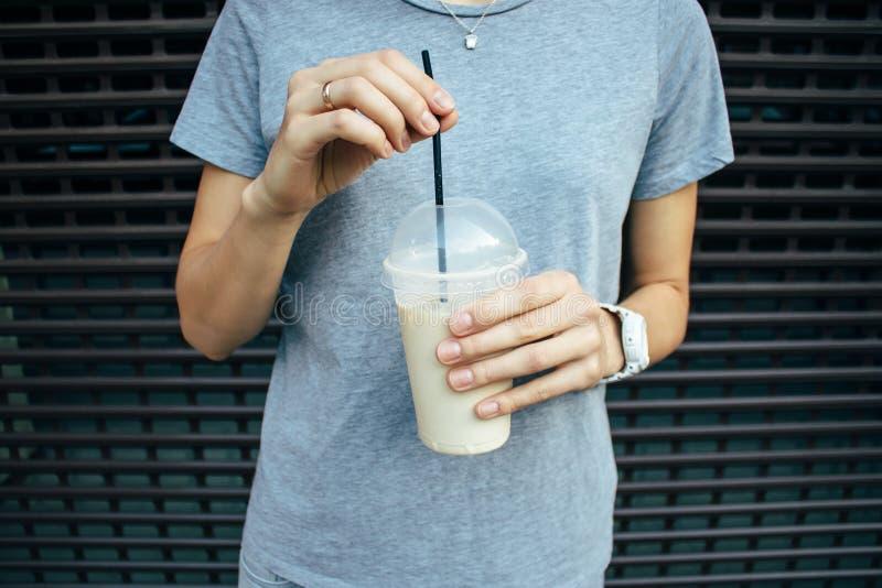 Jovem mulher que guarda o latte do café no copo transparente plástico fotos de stock