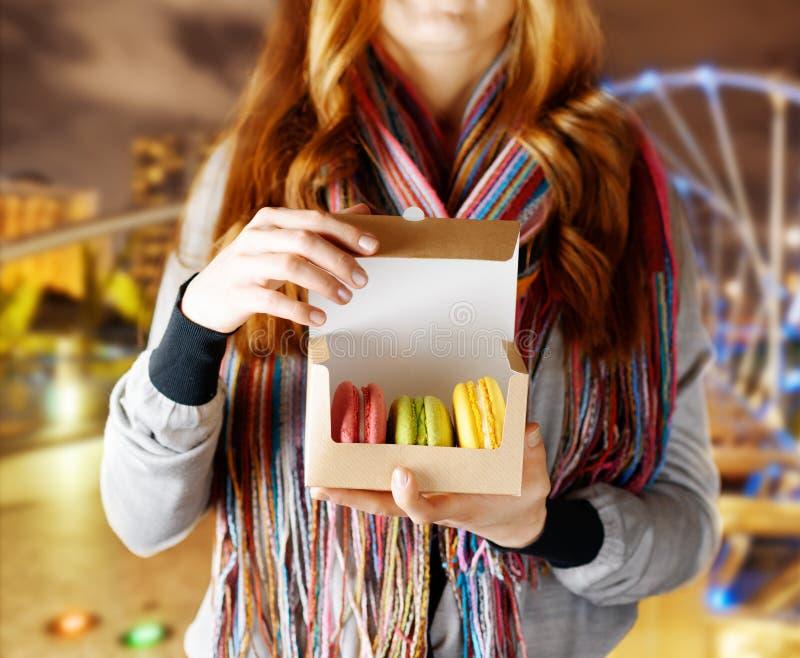 Jovem mulher que guarda o macaron da pastelaria francesa no café fotos de stock