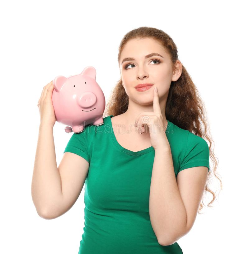 Jovem mulher que guarda o mealheiro no fundo branco Conceito das economias do dinheiro imagem de stock