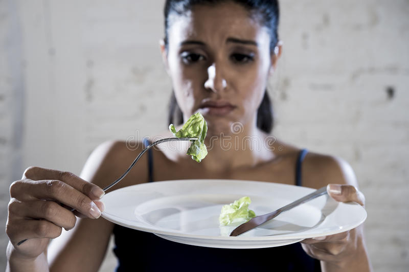 Jovem mulher que guarda o prato com alface ridícula como seu símbolo do alimento da desordem de nutrição louca da dieta fotos de stock royalty free