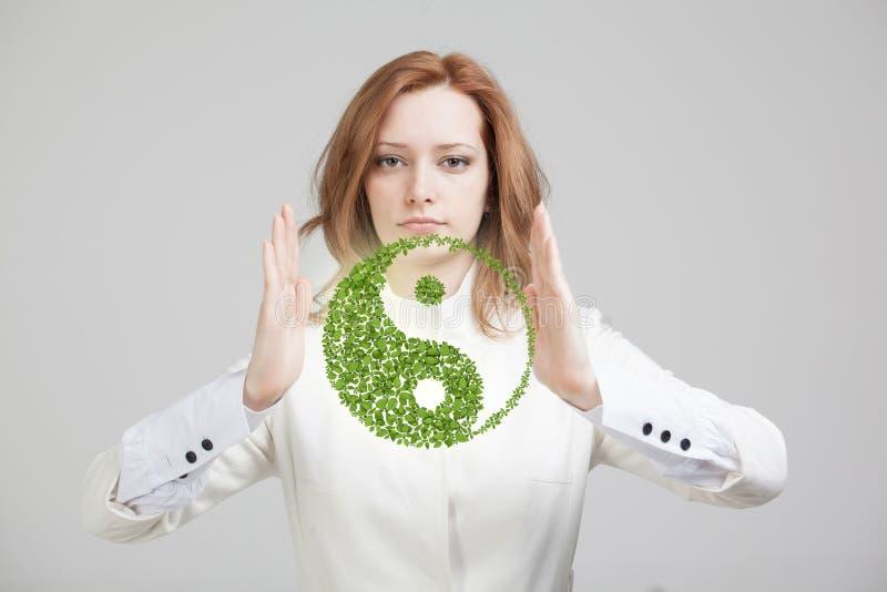 Jovem mulher que guarda o símbolo ying de yang imagem de stock