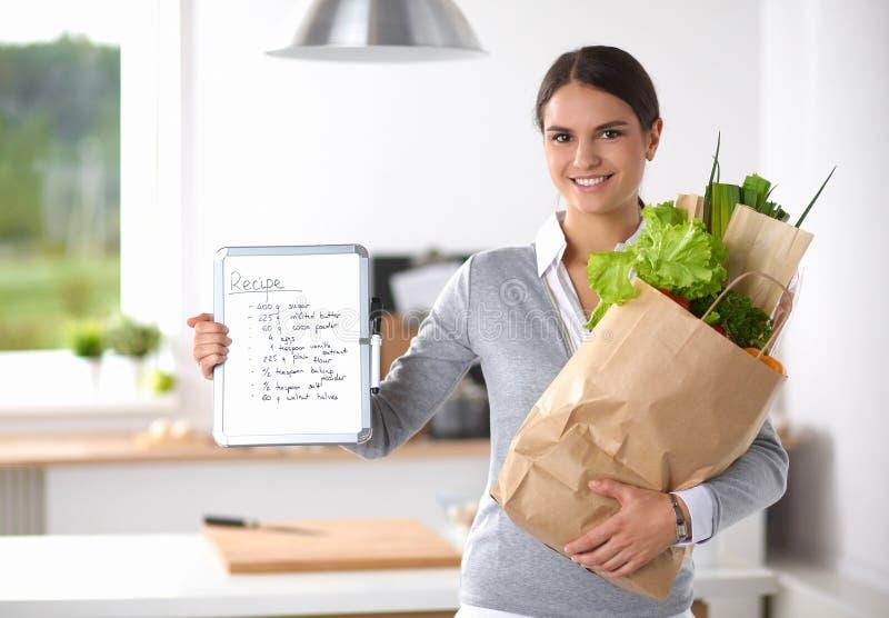 Jovem mulher que guarda o saco de compras na mercearia com foto de stock royalty free