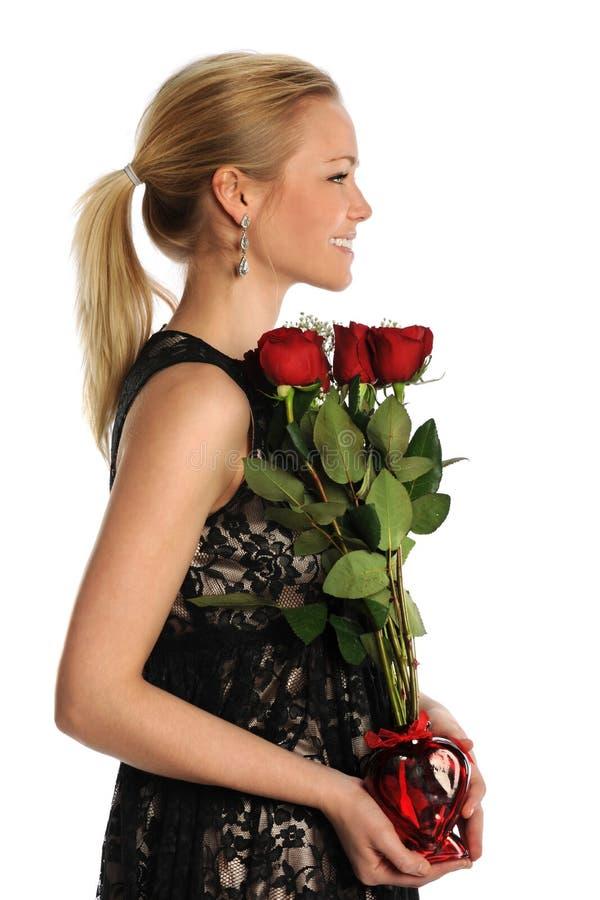 Jovem mulher que guarda o vaso com rosas imagens de stock