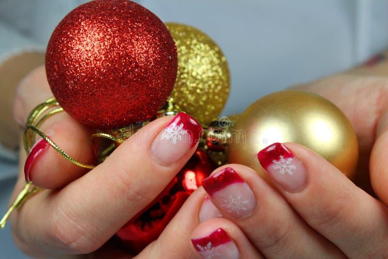 Jovem mulher que guarda ornamento do Natal em suas mãos fotos de stock royalty free