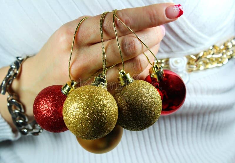 Jovem mulher que guarda ornamento do Natal em suas mãos imagens de stock royalty free