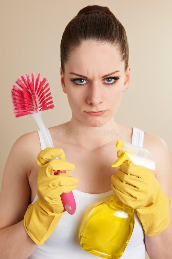 Jovem mulher que guarda os produtos de limpeza que olham infelizes imagem de stock royalty free