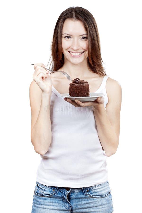 Jovem mulher que guarda a parte de bolo de chocolate fotografia de stock