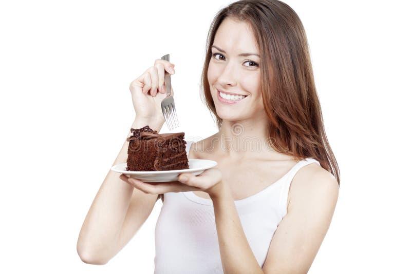Jovem mulher que guarda a parte de bolo de chocolate imagens de stock
