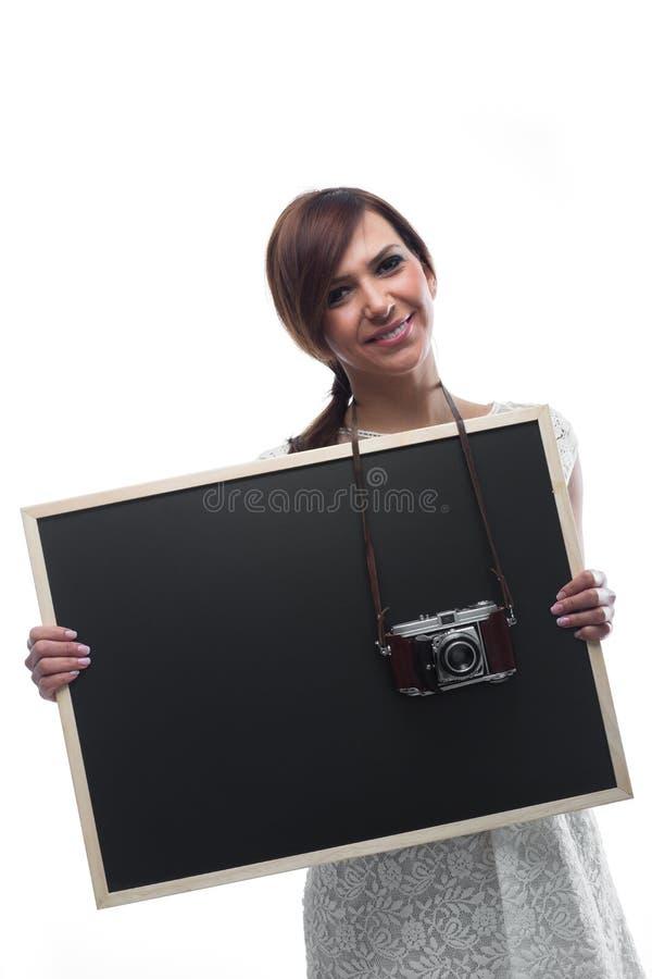 Jovem mulher que guarda a placa com a câmera em torno do pescoço fotografia de stock royalty free