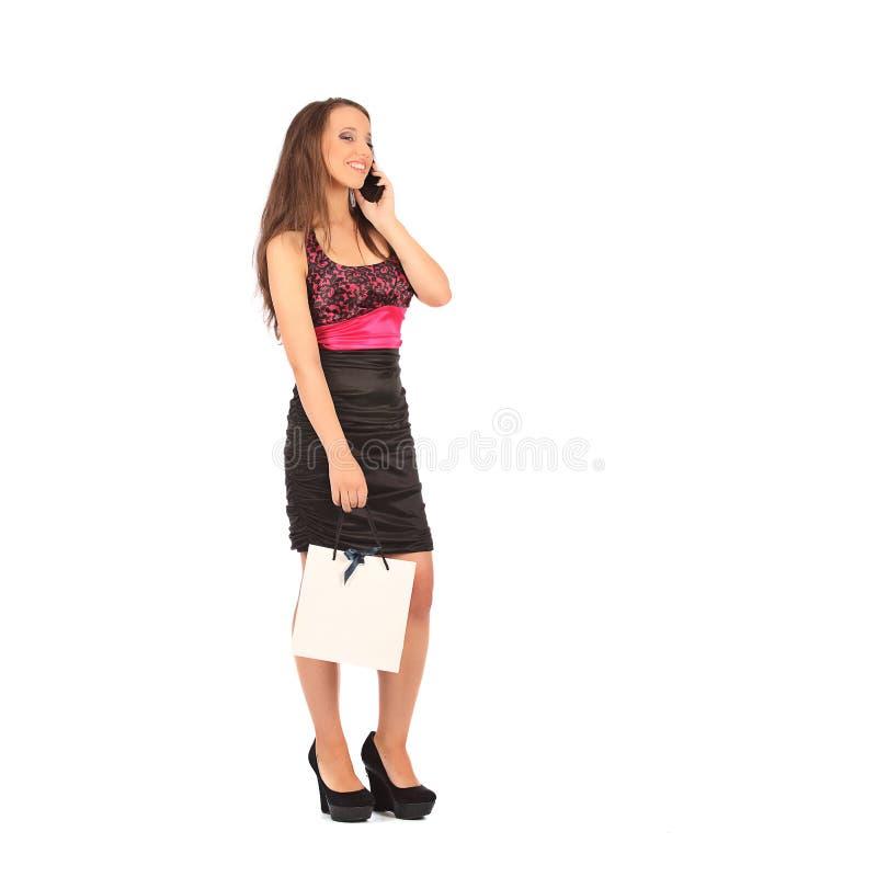 Jovem mulher que guarda sacos de compras e que fala em um telefone celular fotos de stock royalty free
