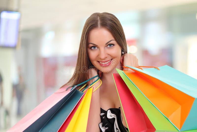Jovem mulher que guarda sacos de compras e que sorri na câmera foto de stock