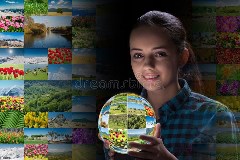 A jovem mulher que guarda a terra com fotos da natureza imagens de stock