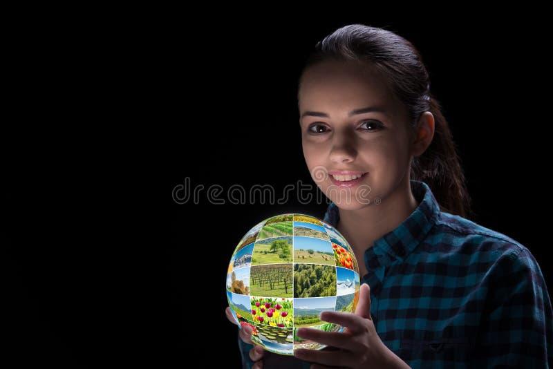 A jovem mulher que guarda a terra com fotos da natureza foto de stock royalty free