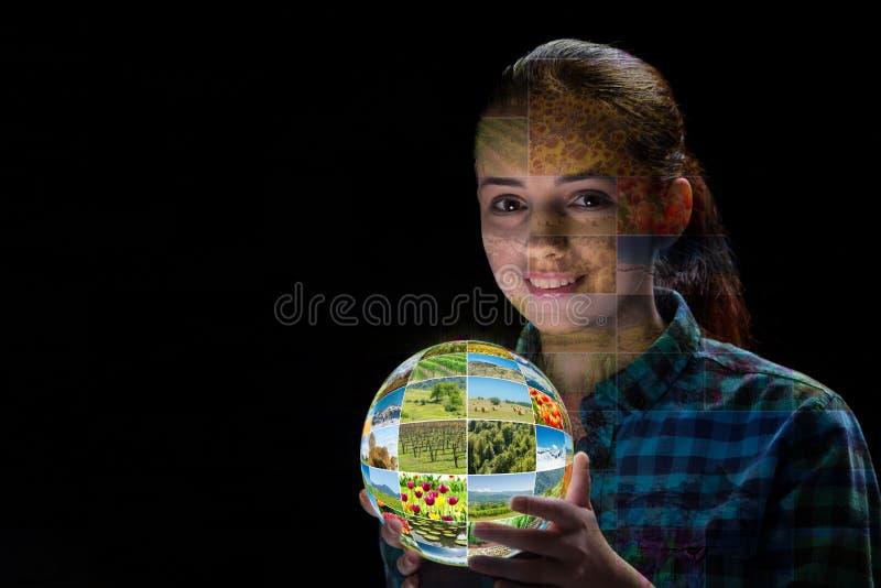 A jovem mulher que guarda a terra com fotos da natureza fotografia de stock