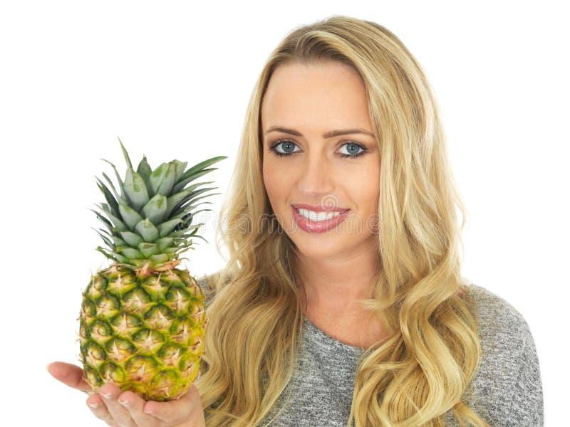 Jovem mulher que guarda um abacaxi fotos de stock royalty free