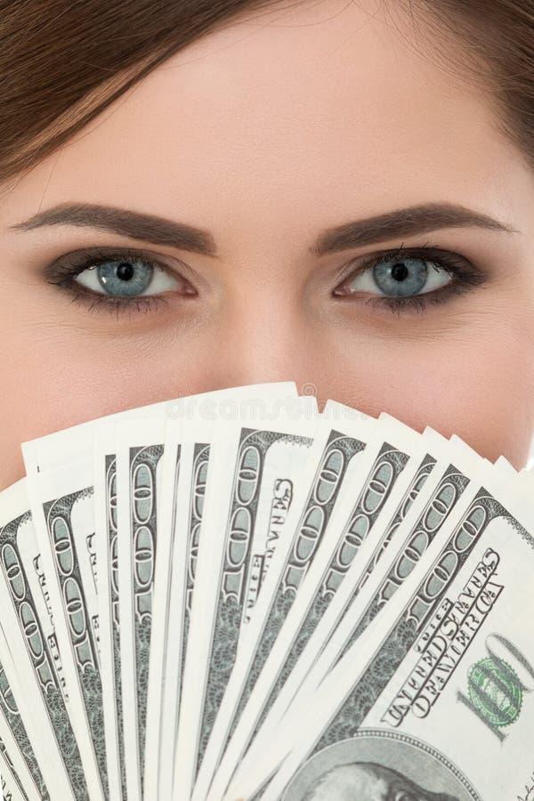 Jovem mulher que guarda um fã de cem retratos das notas de dólar imagens de stock royalty free