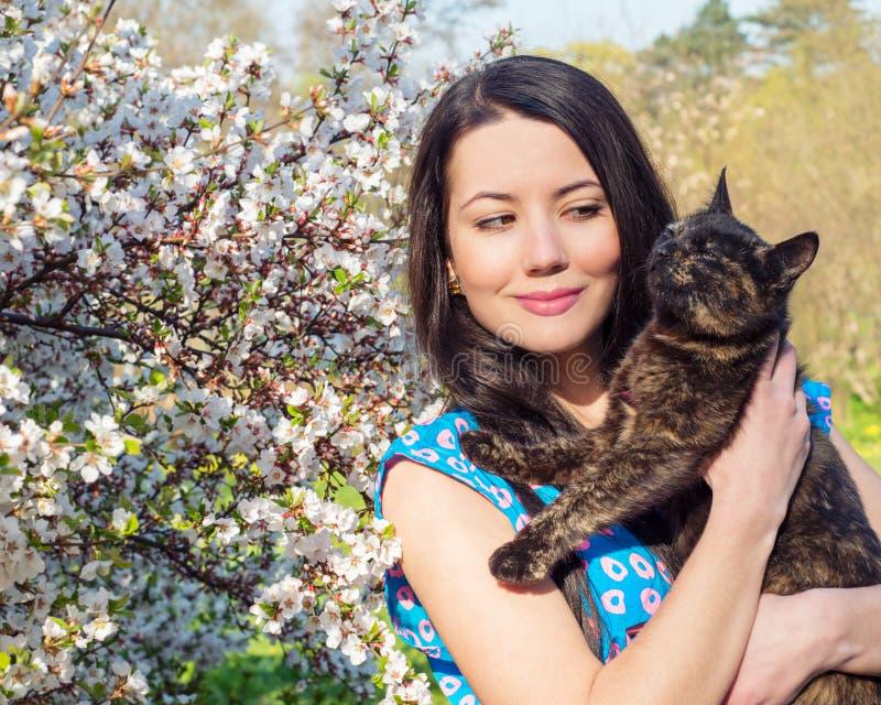 Jovem mulher que guarda um gato fotos de stock royalty free