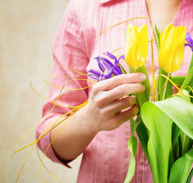 Jovem mulher que guarda um ramalhete da flor imagens de stock royalty free