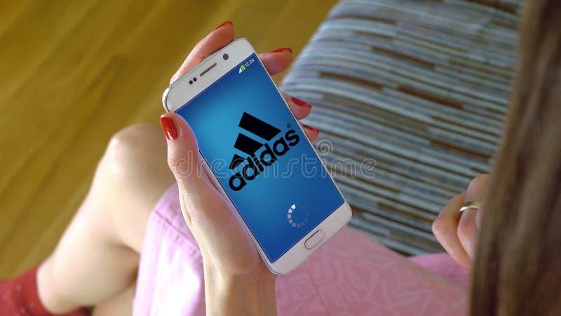 Jovem mulher que guarda um telefone celular com carregamento de Adidas app móvel Cgi conceptual do editorial imagens de stock royalty free