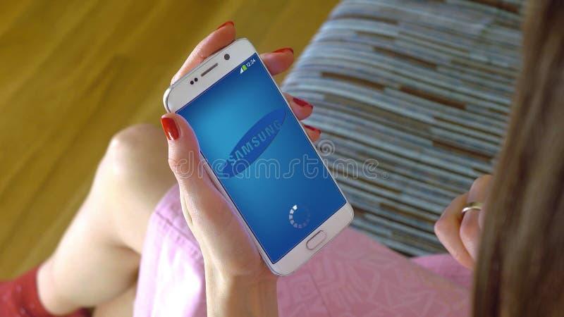 Jovem mulher que guarda um telefone celular com carregamento de Samsung app móvel Cgi conceptual do editorial fotos de stock royalty free