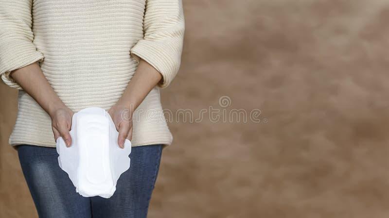 Jovem mulher que guarda uma almofada menstrual foto de stock