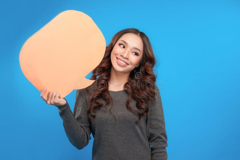 Jovem mulher que guarda uma bolha do discurso em um fundo azul fotografia de stock royalty free