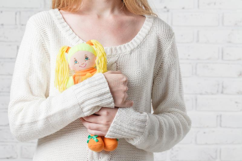 Jovem mulher que guarda uma boneca Deixando a infância foto de stock royalty free