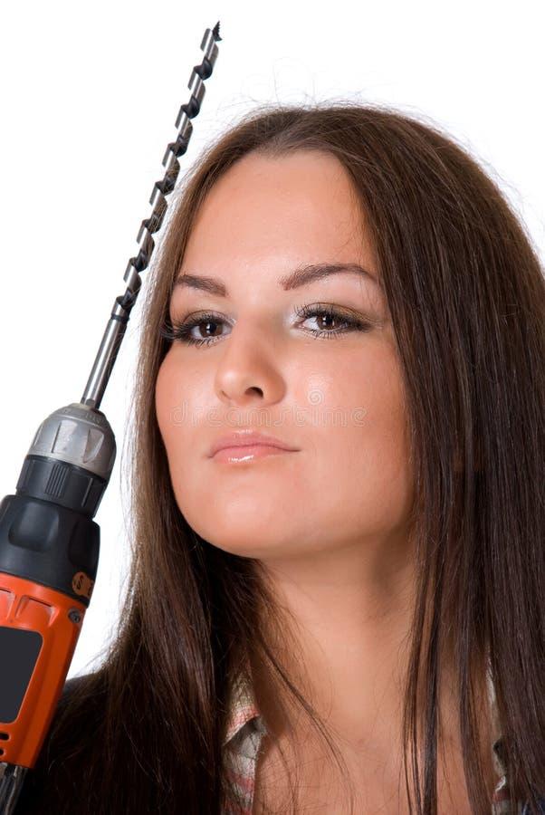 Jovem mulher que guarda uma broca elétrica sem corda Isolado no branco imagem de stock