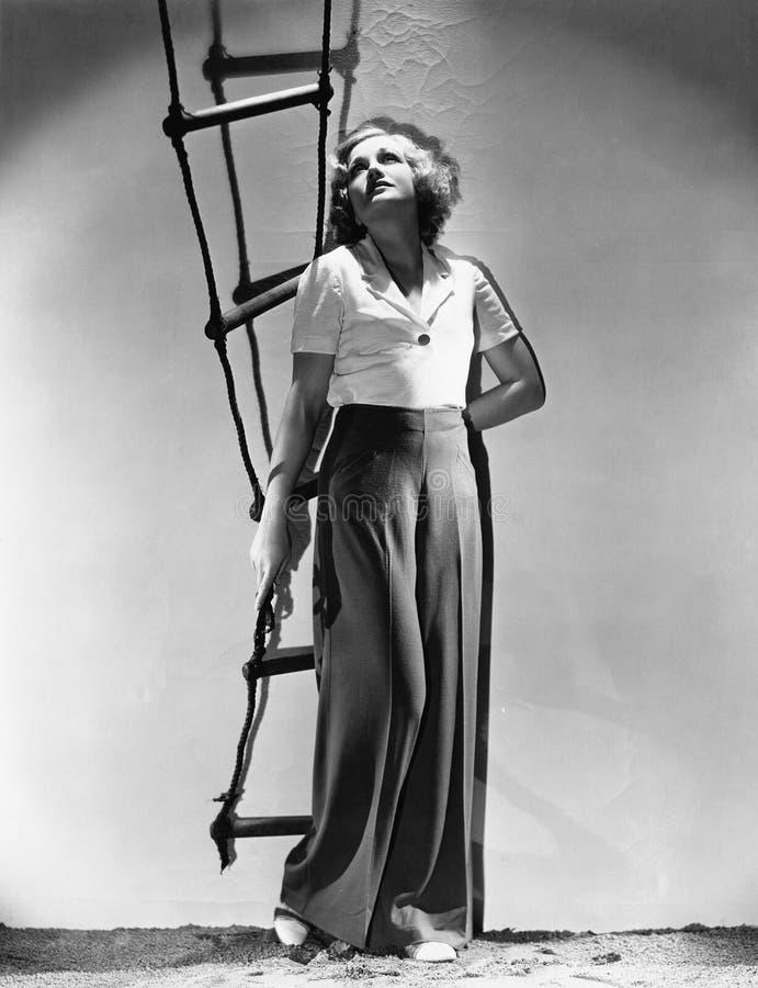 Jovem mulher que guarda uma escada de corda e que olha acima (todas as pessoas descritas não são umas vivas mais longo e nenhuma  imagens de stock royalty free