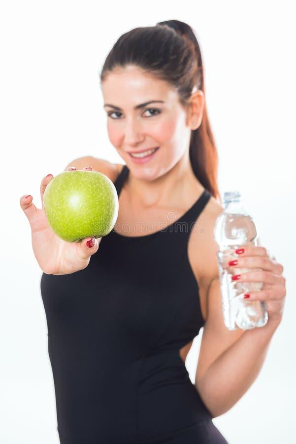 Jovem mulher que guarda uma maçã no fundo branco foto de stock