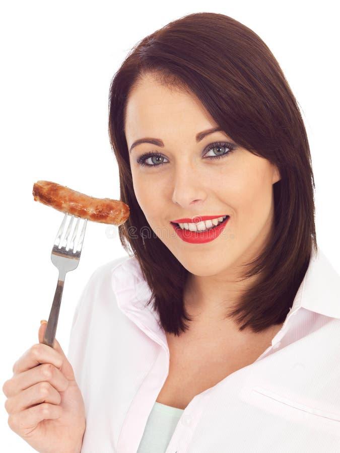 Jovem mulher que guarda uma salsicha de carne de porco em uma forquilha imagens de stock