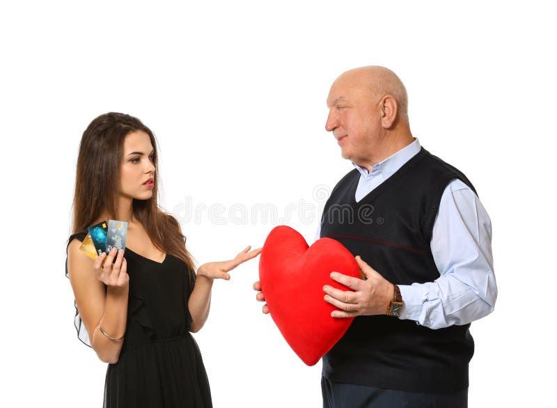 Jovem mulher que guardam cartões de crédito e homem superior com coração vermelho no fundo branco Uni?o de conveni?ncia fotografia de stock royalty free