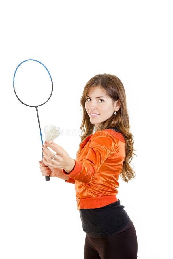 Jovem mulher que guardam a peteca e raquete que joga o badminton imagem de stock royalty free