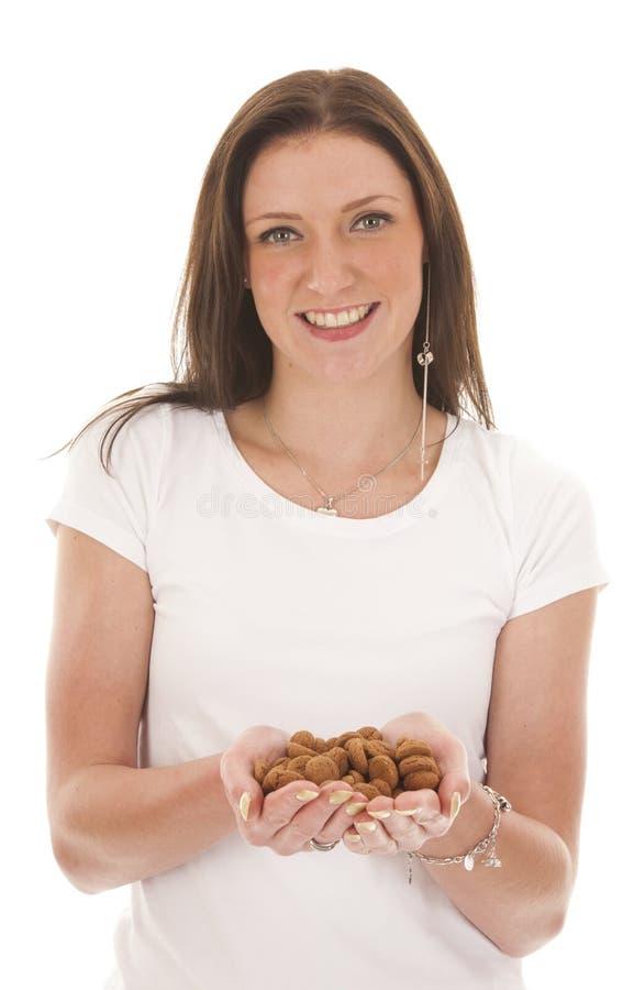 A jovem mulher que guardara doces holandeses típicos pepernoten isolado imagem de stock