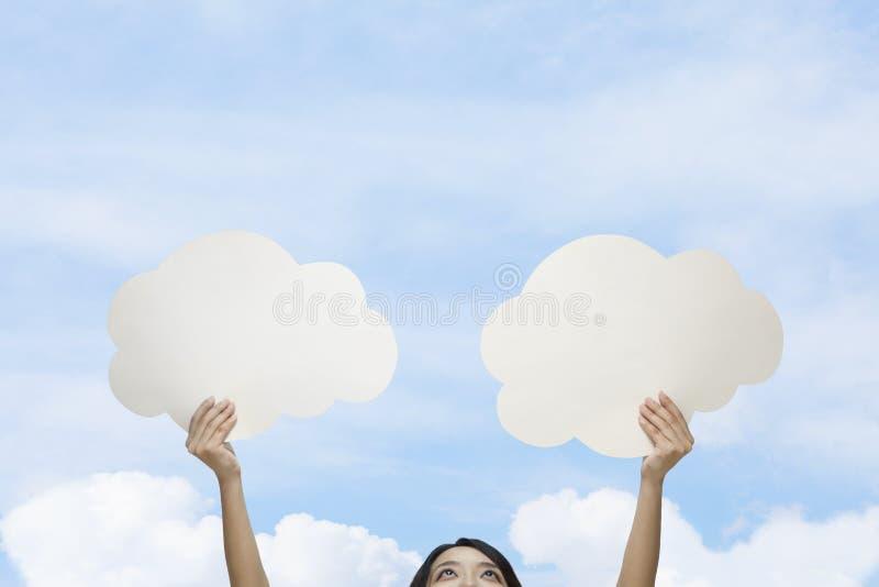 A jovem mulher que guardara dois cortou as nuvens de papel contra um céu azul com nuvens foto de stock