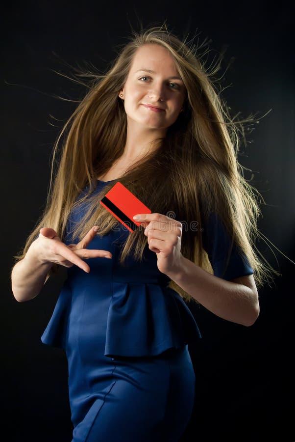 Jovem mulher que guardara o cartão de crédito vermelho fotografia de stock royalty free